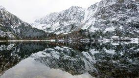Bezinningen in het kalme meerwater met sneeuw en bergen Royalty-vrije Stock Afbeeldingen