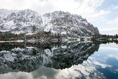 Bezinningen in het kalme meerwater met sneeuw en bergen Royalty-vrije Stock Foto's