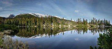 Bezinningen in het kalme meerwater met sneeuw en bergen Stock Foto's