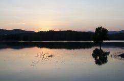 Bezinningen over het meer bij zonsondergang Stock Foto's