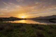 Bezinningen over het meer bij zonsondergang Stock Afbeeldingen