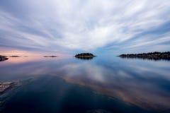 Bezinningen van een bewolkte hemel op het meer Het meer van de spiegelzomer Het meer van Ladoga in Karelië stock foto