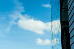 Bezinningen van gebouwen om de blauwe hemel en de wolken mooi te zien kijken Royalty-vrije Stock Afbeeldingen