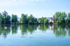 Bezinningen van het park en de huizen in het meer Stock Foto