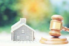 Bezitsveiling, Hamer houten en modelhuis op natuurlijke groene onroerende goederen achtergrond, advocaat van huis en eigendomsbez stock afbeelding