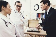 Beznadziejny biznesmen oferuje udział pieniądze wykwalifikowana lekarka lekarstwo dolegliwość obraz royalty free