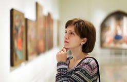 Bezoeker die beelden in kunstgalerie kijken stock foto's