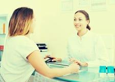 Bezoeker raadplegende arts in esthetisch geneeskundecentrum royalty-vrije stock afbeelding