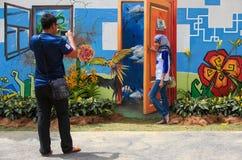 Bezoekers die foto met de muurschilderijen van het aardthema en echte bloem nemen Royalty-vrije Stock Foto