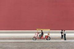 Bezoekers tegen een massieve rode muur van Paleismuseum Stock Foto's