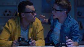 Bezorgde multi-etnische vrienden die videospelletje verliezen, die elkaar, verslaving beschuldigen stock videobeelden