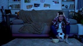 Bezorgde tiener het letten op voetbalwedstrijd op TV ongelukkig met team het verliezen, sport royalty-vrije stock afbeelding