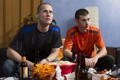 Bezorgde twee terwijl het letten van sporten op spel op horizontale TV, Royalty-vrije Stock Foto