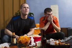 Bezorgde twee terwijl het letten van sporten op spel op verticale TV, Stock Foto's