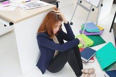 Bezorgde verstoorde jonge Aziatische bedrijfsvrouw met handen op hoofdzitting op vloer bij haar in werkplaats van bureau stock foto
