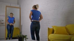 Bezorgde vrouw die jeans met inspanning proberen dicht te knopen stock videobeelden