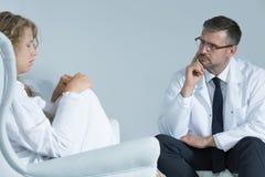Bezorgde vrouw met een psychiater stock afbeeldingen