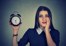 Bezorgde vrouw met wekker Het concept van de tijddruk stock afbeeldingen