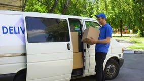 Bezorger die pakketdoos van bestelwagen, het bedrijf van de koeriersdienst, bewegende firma nemen stock video