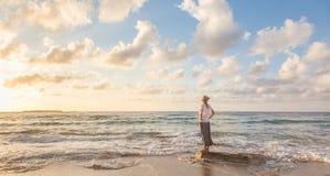Bezpłatna Szczęśliwa kobieta Cieszy się zmierzch na Piaskowatej plaży Zdjęcie Stock