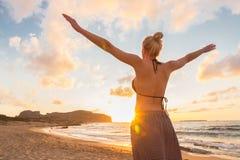 Bezpłatna Szczęśliwa kobieta Cieszy się zmierzch na Piaskowatej plaży Zdjęcie Royalty Free
