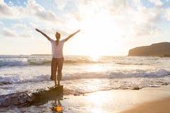 Bezpłatna Szczęśliwa kobieta Cieszy się zmierzch na Piaskowatej plaży Obraz Royalty Free