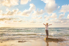 Bezpłatna Szczęśliwa kobieta Cieszy się zmierzch na Piaskowatej plaży Fotografia Royalty Free