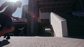 Bezpłatni biegacze wykonuje parkour w miastowej przestrzeni