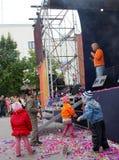 Bezpłatny koncert, piosenkarza bard, dzieci bawić się blisko sceny i widowni, otwarta scena (country rock muzyka) Zdjęcie Stock