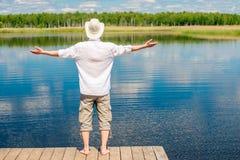 Bezpłatny szczęśliwy mężczyzna cieszy się piękną naturę blisko jeziora obraz royalty free