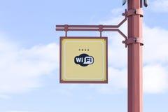 Bezpłatny WiFi - bezprzewodowy interneta znak na słupie na niebieskiego nieba tle Obraz Stock