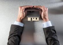 Bezpieczny izolacja dom z biznesmen rękami ochrania dach i zabezpiecza Obraz Royalty Free