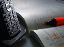 Bezprzewodowy telefon i podręcznik na stole Zdjęcia Stock