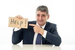 Bezradny dojrzały biznesmen trzyma pomoc i depresji pojęcie odizolowywającego w bielu podpisywać wewnątrz kryzysu finansowego bez obrazy royalty free