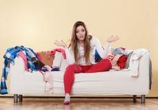 Bezradny kobiety obsiadanie na kanapie w upaćkanym pokoju domu Obrazy Royalty Free