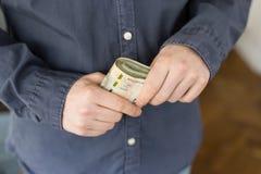 Bezrobotnego mężczyzny mienia pieniądze od połysk zasiłków socjalnych fotografia royalty free