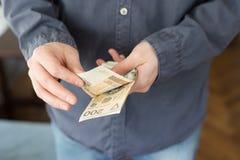 Bezrobotnego mężczyzny odliczający pieniądze od połysk zasiłków socjalnych obrazy royalty free
