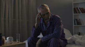 Bezsenny starszego mężczyzna cierpienie od migreny, bierze środki przeciwbólowych przy nocą zbiory wideo