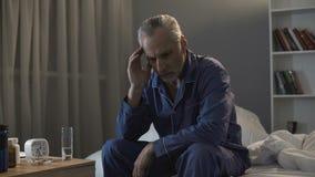 Bezsenny starszego mężczyzna cierpienie od migreny, siedzi na kanapie przy nighttime obraz royalty free