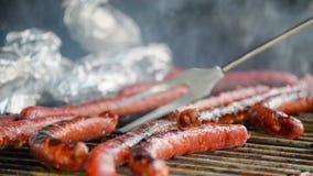 Bezszwowa pętla - Rozwidla obracać nad smakowitymi soczystymi kiełbasami piec na grillu na grillu z grulami w folii, wideo HD zbiory wideo