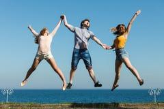 Beztroscy przyjaciele skacze denną ocean wodą zdjęcie royalty free