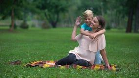 Beztroska chłopiec przytulenia matka w parku, ogólnospołeczny program dla samotny rodzic rodziny zbiory