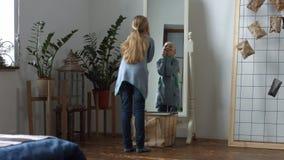 Beztroska mała dziewczynka robi śmiesznym twarzom w lustrze zbiory