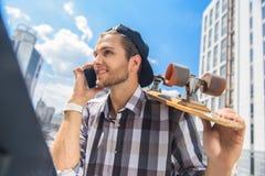 Beztroski młody człowiek opowiada na smartphone Fotografia Royalty Free