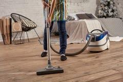 Beztwarzowa środkowa sekcja młoda kobieta używa próżniowy czystego w domowej żywej izbowej podłodze, robić czyści obowiązek domow zdjęcie stock