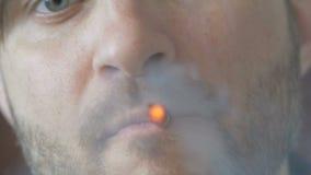 Beztwarzowy mężczyzna zaświeca papieros w pokoju zbiory