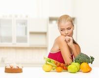 Bezweifeln der Frau mit Früchten und Torte Stockfoto