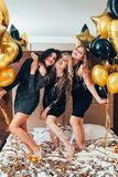 Bff hangout urban girls leisure lifestyle confetti. BFF hangout. Urban girls leisure and lifestyle. Glitter confetti and balloons decor. Young women in black royalty free stock image