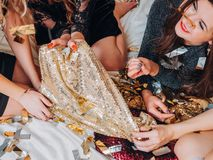 Bff night party leisure females sequin outfit. BFF night out plans. Party leisure time. Females lying on bed choosing sequin outfit. Glitter confetti around. Fun royalty free stock image