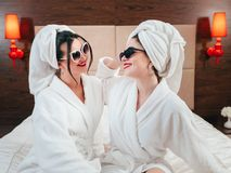 Bff spa beauty care females bathrobes smiling. BFF. Spa beauty care and treatment. Two young females in bathrobes smiling. Towels on heads. Hotel room interior stock photo